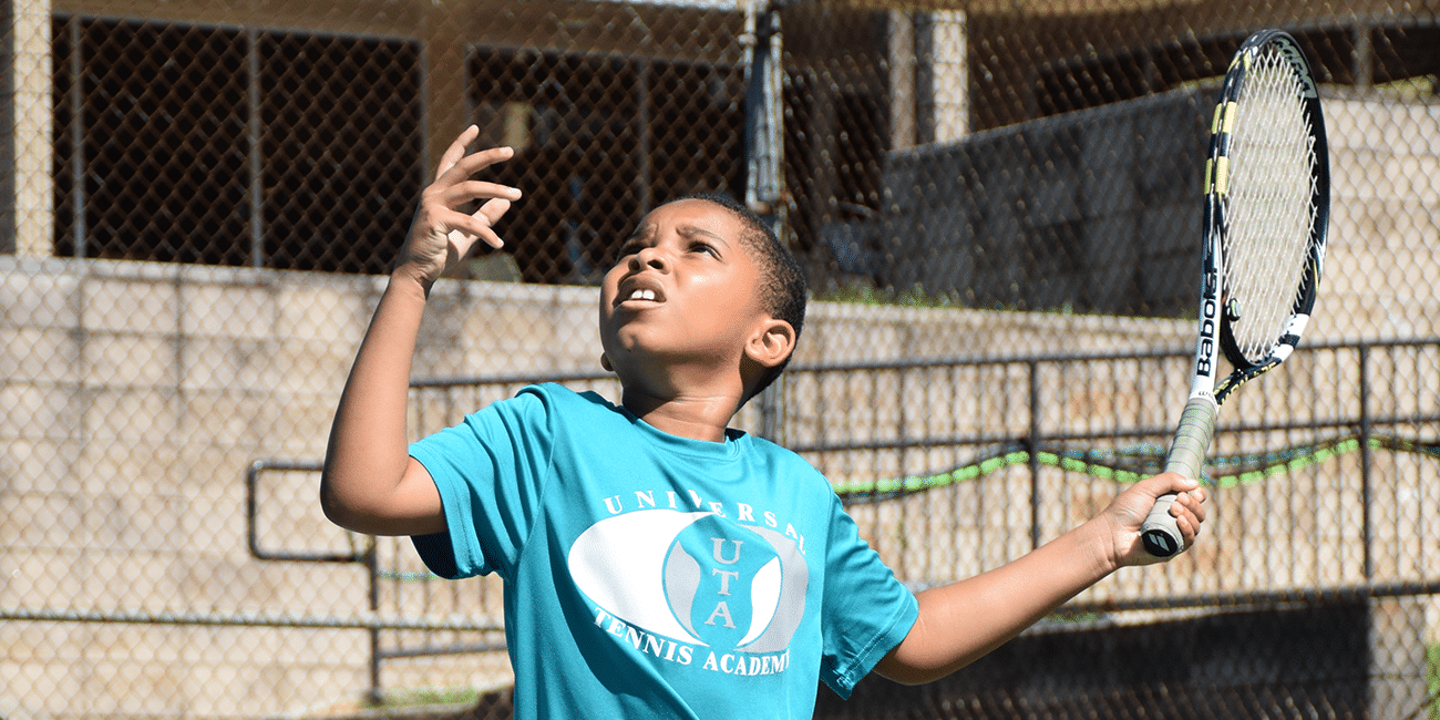 UTA (Universal Tennis Academy) McGhee Junior Program Boy Blue Shirt Serving